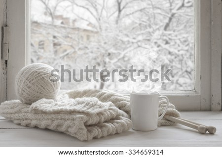 Cozy winter still life: mug of hot tea and warm woolen knitting on vintage windowsill against snow landscape from outside. - stock photo