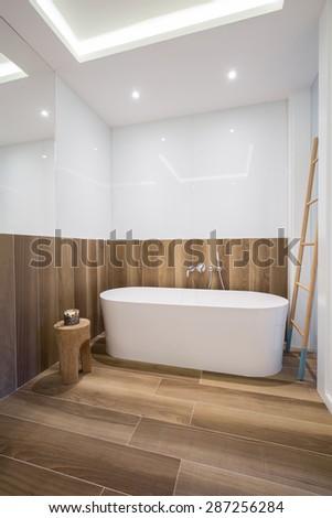 Cozy wooden bathroom with white porcelain bathtub - stock photo