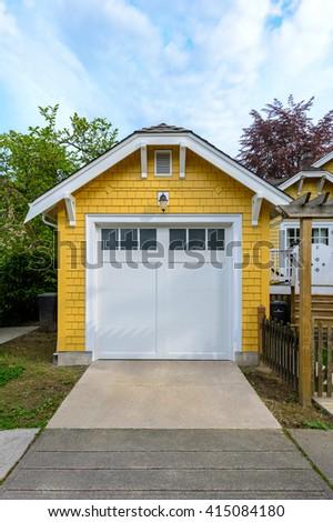 Cozy yellow garage with white doors. - stock photo