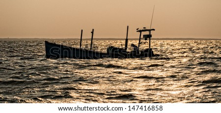 Crab boat in silhouette in the early morning light on the Chesapeake Bay. - stock photo