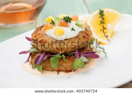 Crab cakes appetizer with two sauces, baby greens, and mango - avocado citrus salsa. Dungeness crab in the background. - stock photo