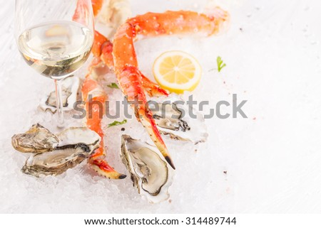 Crab cluster and oysters on crushed ice with glass of white wine - stock photo
