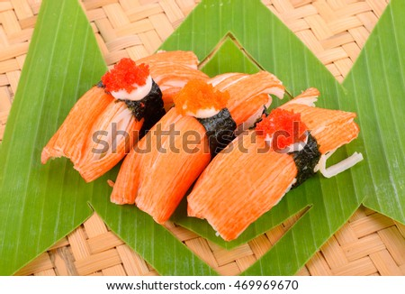 Crab crab sushi pieces on a wooden floor.