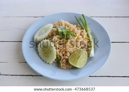 Crab Fried Rice of Thai foods in blue dish on wooden background.