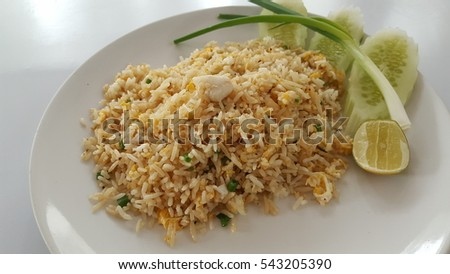 Crab fried rice with egg, sided with a slice of lemon, spring onion and sliced cucumbers isolated on white plate.