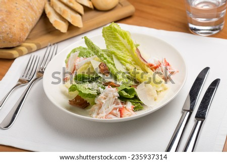 Crab salad with bread and water on wooden table