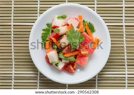 Crab stick spicy salad with vegetable on wood background - stock photo