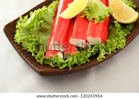 Crab sticks with lettuce leaves and lemon on plate, close up