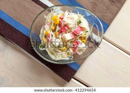 Crab sticks with rice noodles in glass bowl on textile - stock photo