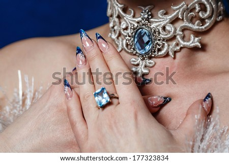 Crack nail polish on female fingers and beautiful jewels shot closeup - stock photo