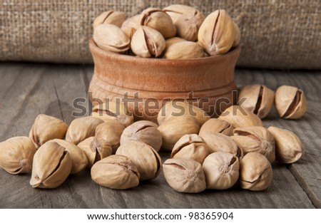 Cracked and Dried Pistachio Nuts In A Wooden Bowl - stock photo