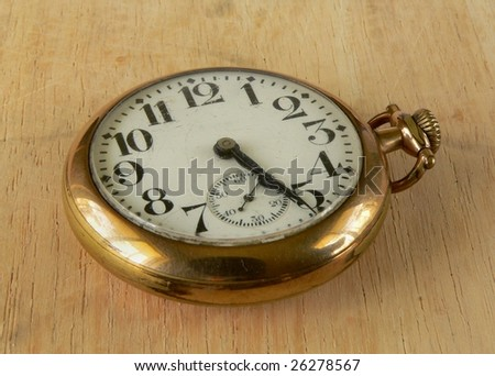 cracked and dusty antique pocket watch on wooden surface