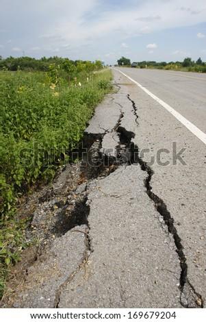 cracked asphalt road after flood ,damaged roadway  - stock photo