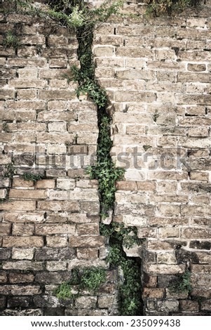 Cracked brick wall - Deep crack in a brick wall - stock photo