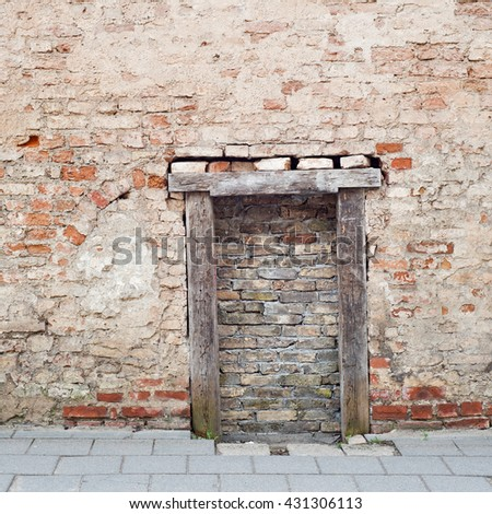 cracked brick wall with bricked up doorway of an abandoned house