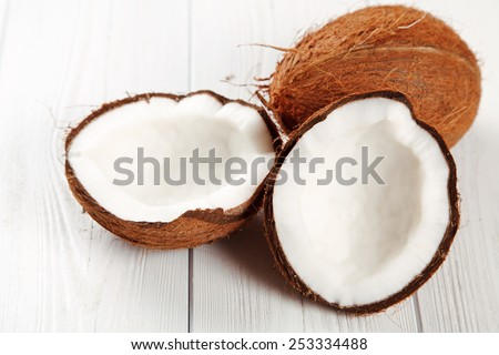 Cracked coconut on wooden table. - stock photo