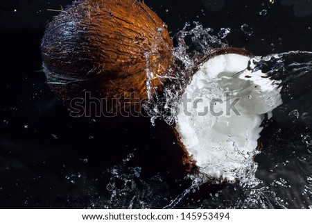 cracked coconut with big splash on black background - stock photo