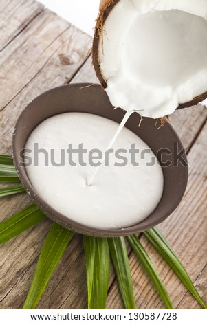 cracked coconut with milk splash in wooden table on white - stock photo