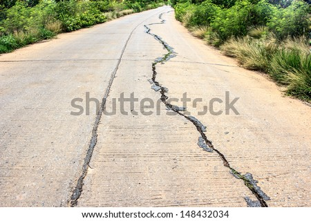 cracked concrete road after earthquake - stock photo