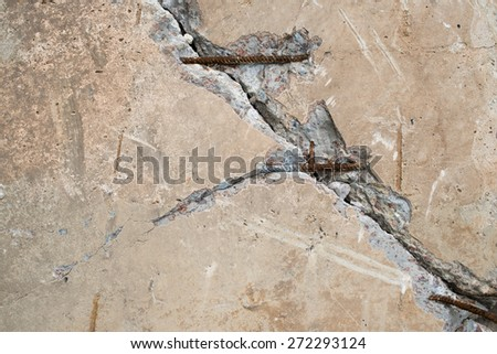 Cracked concrete surface with visible reinforcement and rich texture. - stock photo