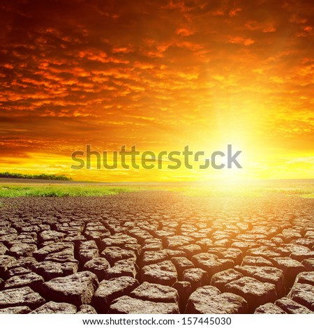 cracked earth and red sunset - stock photo