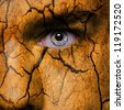 Cracked earth pattern on man face - stock photo