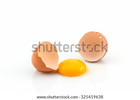 Cracked egg and shell on a white background. Broken chicken egg.   - stock photo