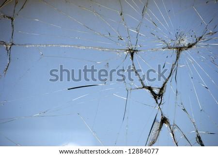 Cracked glass on blue background - stock photo