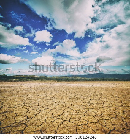 Cracked ground and cloudy scay. Natural disaster landscape, toned like Instagram filter