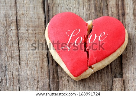 Cracked heart shaped cookie decorated with red icing as a concept of broken heart, breakup and end of relationship - stock photo