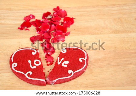 Cracked heart shaped cookie decorated with red icing as a concept of broken heart, breakup and end of relationship, rose petals. - stock photo