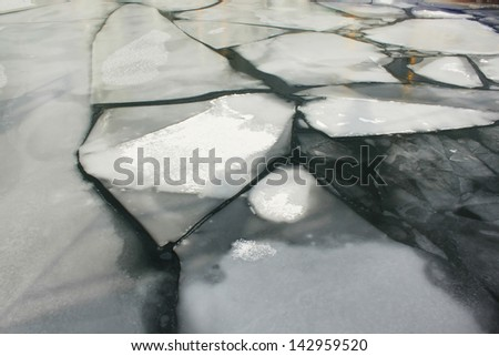 Cracked ice on a frozen lake - stock photo