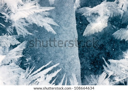Cracked ice surface of thick ice layer on lake with beautiful large hoar-frost ice crystals - stock photo