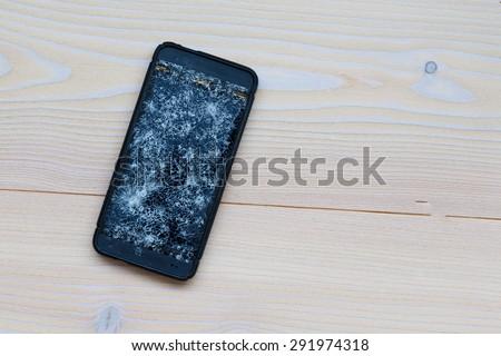 Cracked mobile phone - stock photo