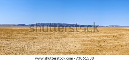 Cracked mud fills a dried lake bed in the Mojave Desert of Southern California. - stock photo