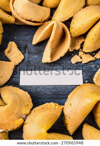 cracked open fortune cookie with blank space on blue wooden background, top view - stock photo