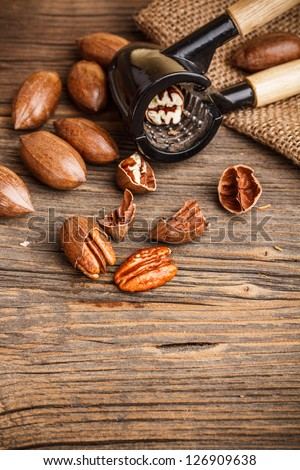 Cracked pecan nuts on rustic wooden table - stock photo