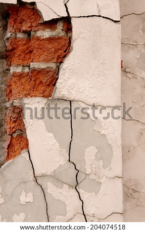 Cracked plaster on brick wall