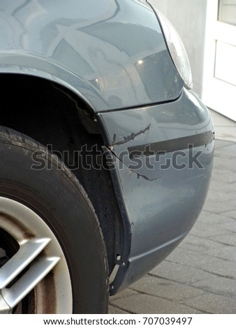 Cracked plastic front bumper on gray color car close up