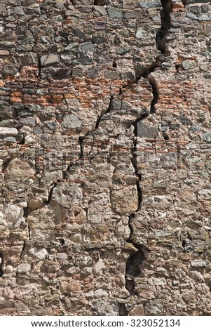 Cracked red brick wall of a medieval fortress - stock photo