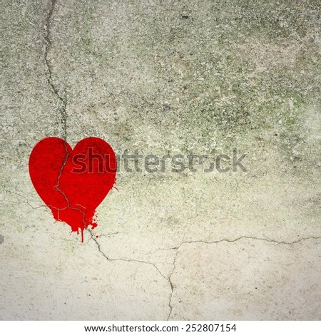Cracked red heart on concrete wall - stock photo