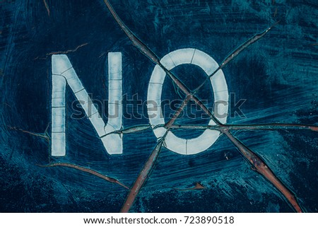 "cracked sign with the word ""no"""