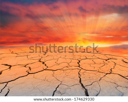 Cracked texture of the earth on sunset. Dry landscape. - stock photo