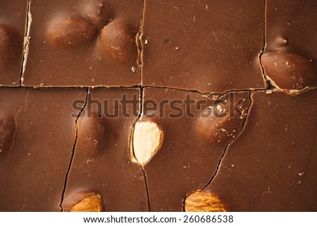 Cracked Tiles Of Milk Chocolate With Almonds - stock photo