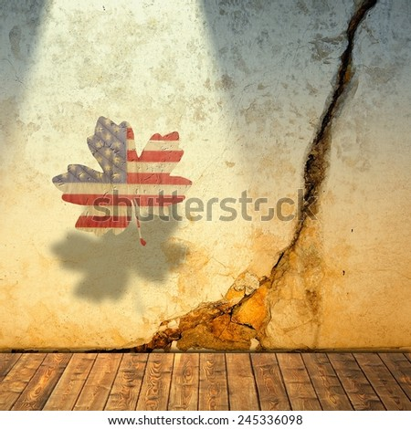 Cracked wall and maple leaf with symbolic american colors - stock photo