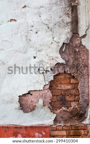 cracked wall with bricks and old plaster - stock photo