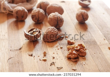 Cracked walnuts on natural wood cutting board