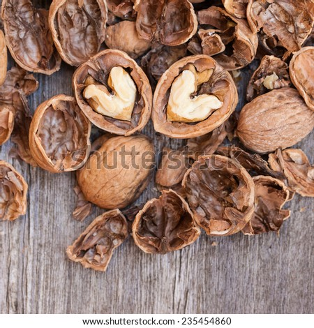 Cracked walnuts on wooden background, close up. Heart shape. Also available in horizontal format.  - stock photo