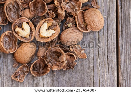 Cracked walnuts on wooden background, close up. Heart shape. Copy space. Also available in square format.