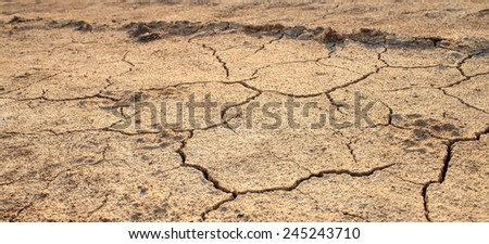 Cracked waterless ground at summer drought . Natural disasters desert background - stock photo